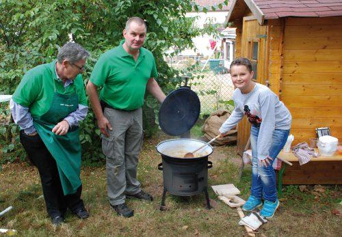 Rüdiger Harth, 2. OGV-Vorsitzender und seine Frau Petra hatten 60 Liter Szegediner Gulasch vorbereitet, das auf einem Kanonenöfchen gekocht wurde. Bereits um 12.30 Uhr hieß es dann: Kessel leer! Auf dem Foto sind Vorstandsmitglied Bearix Jung, Rüdiger und Sebatian Harth.
